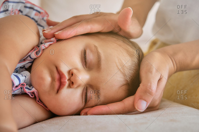 Portrait of a little girl sleeping protected by cropped unrecognizable mother's hands in a sofa