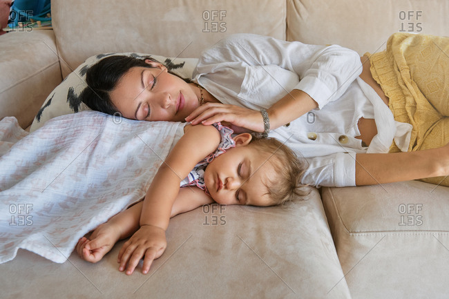 Mother and little girl covered with a blanket sleeping together on the sofa at home