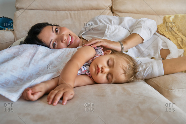 A little girl sleeping with her mother lying on a sofa while facing the camera