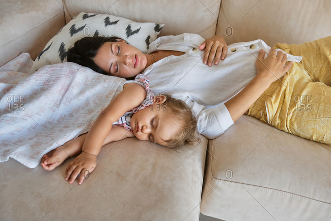Woman and little girl covered with a blanket sleeping together on the sofa at home