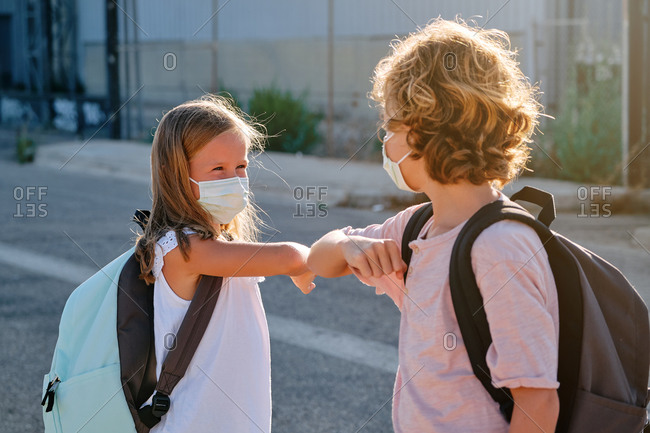Two kids with school bags and masks greeting each other with a gesture of touching elbows outdoors