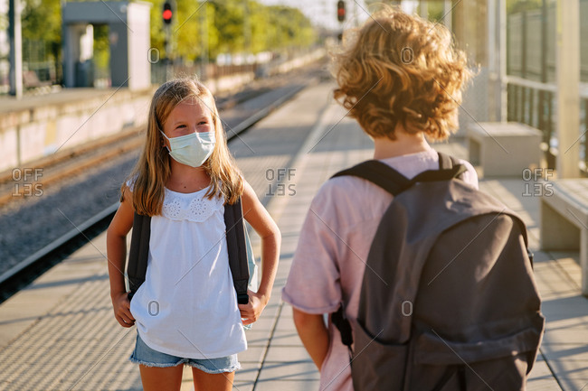 Two children with black school bags and mask talking from a distance while waiting for the train on a station platform in the morning