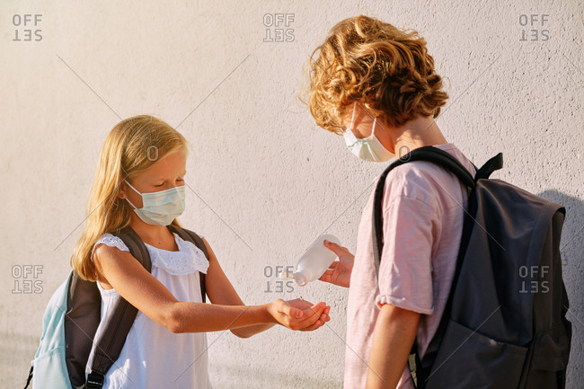 Boy with black school bag and mask throwing disinfectant gel on the hands of a girl wearing a mask in the street