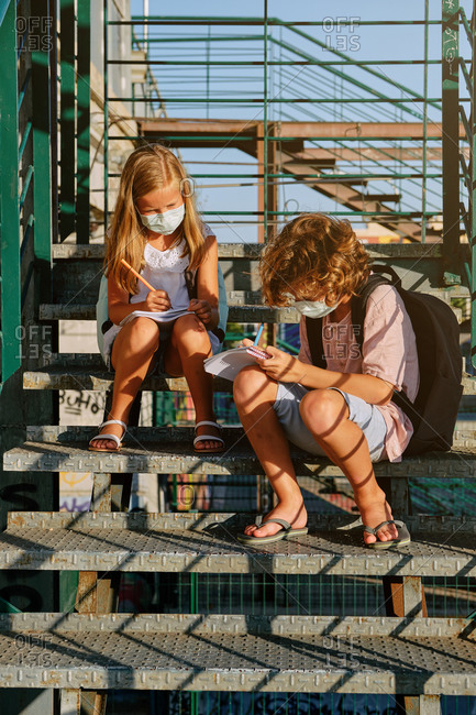 Vertical photo of two children with masks and school bags sitting on an industrial staircase doing their homework on a sunny day