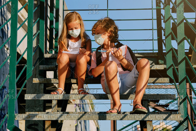 Children with masks and school bags sitting next to a girl on an outside staircase while copying her homework on a sunny day