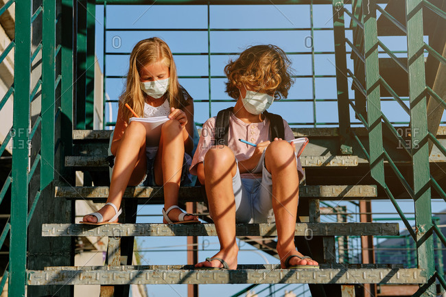 Two children with masks and school bags sitting on an industrial staircase doing their homework together on a sunny day