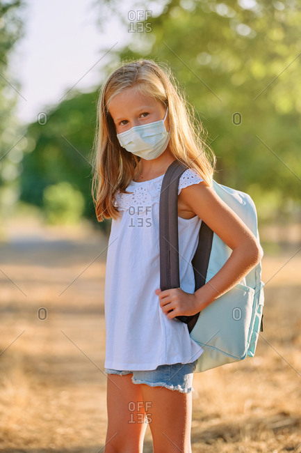Vertical photo of a portrait of a blonde girl with a mask and a school bag looking at a camera in the middle of nature