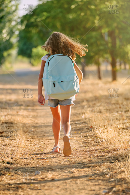 Vertical photo of the portrait of the back of a blond girl with a blue school bag walking along a tree path