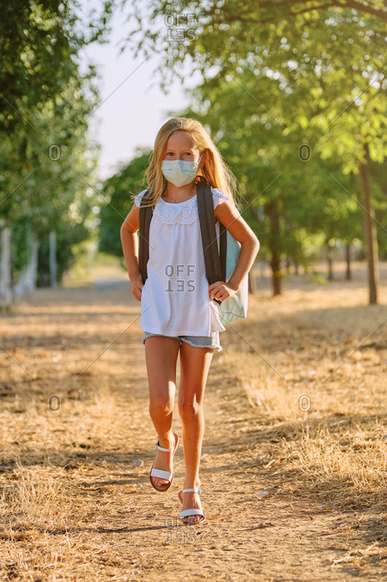 Vertical photo of the portrait of a blond girl with a mask and school bag walking along a tree path while facing the camera