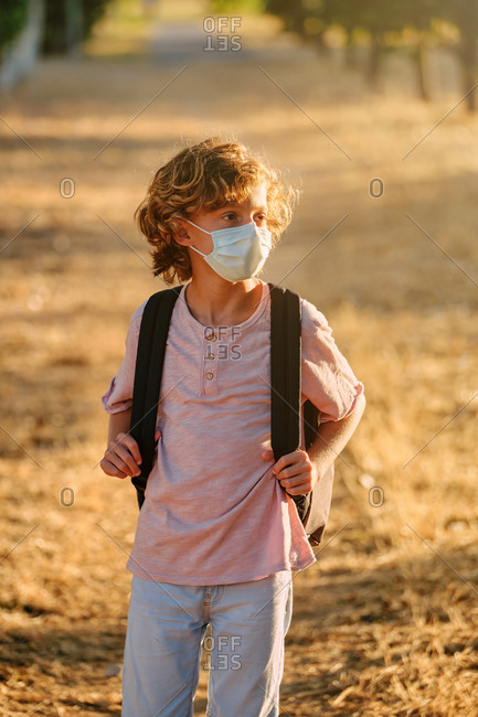 Vertical photo of the portrait of a blond boy with curly hair wearing a mask and school bag while walking along a path