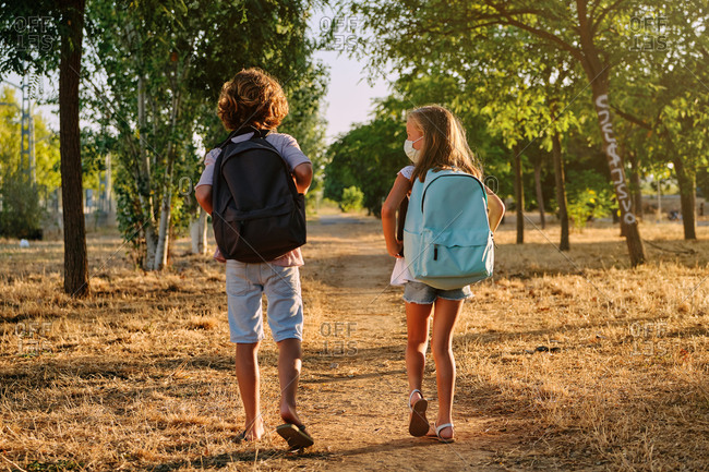 Two children with school bags and a mask on their backs walking along a path in the woods while talking