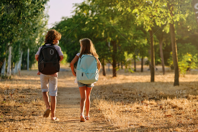 Two kids with school bags and a mask on their backs walking along a path in the woods while talking