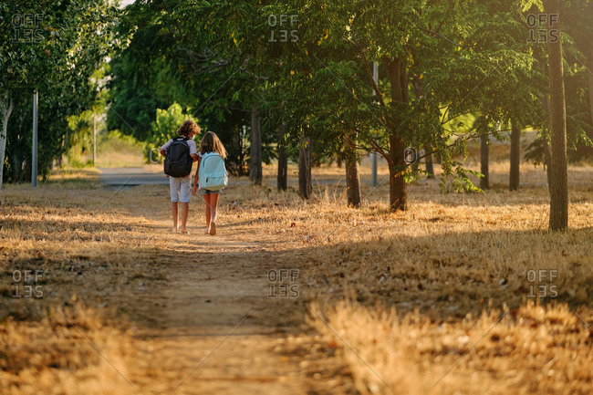 Two kids with school bags and a mask on their backs walking far away along a path in the woods while talking