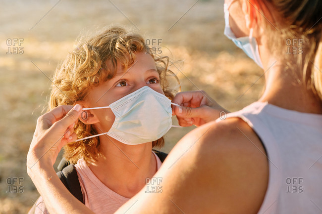 Face of a blond boy with curly hair while an adult helps to put a mask on him outdoors
