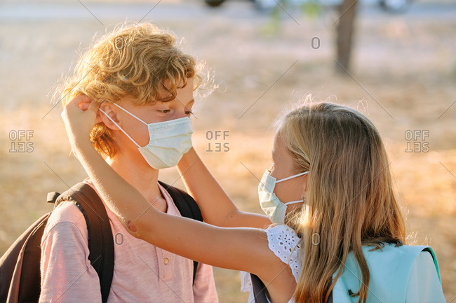 Blond little girl with a school bag and a mask helping a boy to put on her mask outdoors