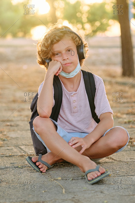 Vertical photo of a blond boy with the mask down and school bag sitting while listening to music with his hand resting on his chin and bored expression facing the camera