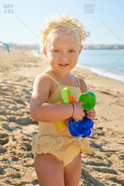 Vertical photo of a little blonde girl in a yellow striped swimsuit standing on the beach with plastic toys in her hand