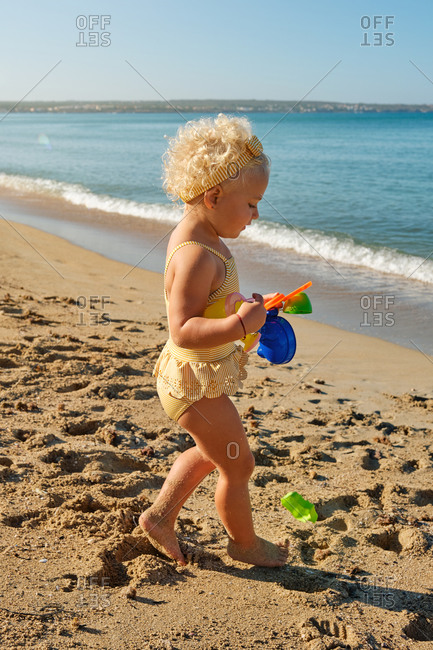 Vertical photo of a little blonde girl in a yellow striped swimsuit walking on the beach with plastic toys in her hand