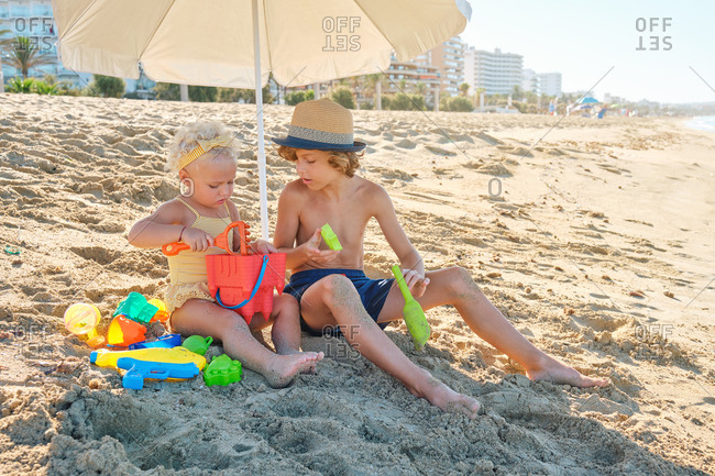 Two children in swimsuits sitting in the sand playing to fill plastic toys with sand under an umbrella at the beach