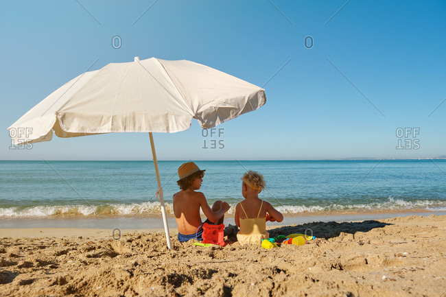 Two children in swimsuits sitting under an umbrella facing the sea and playing in the sand