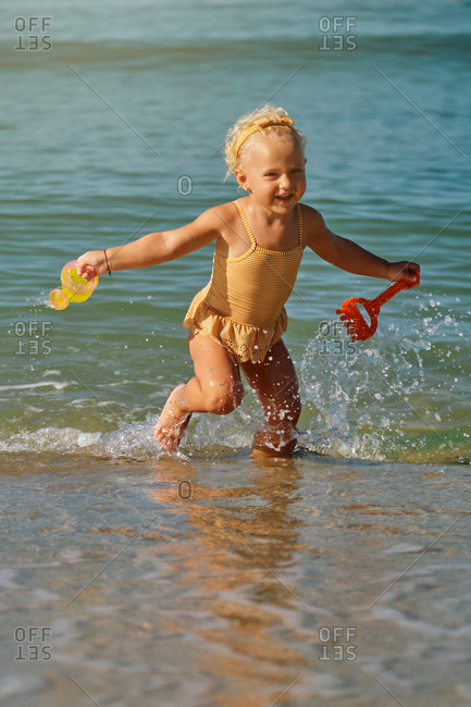 Vertical photo of a girl in a yellow and white striped swimsuit running inside the sea with plastic toys in her hand and a watering can