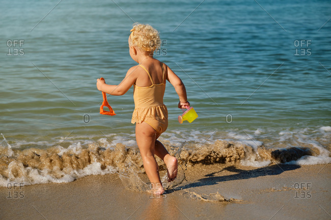 Little girl in a yellow and white striped swimsuit running towards the sea with plastic toys in her hand and a watering can