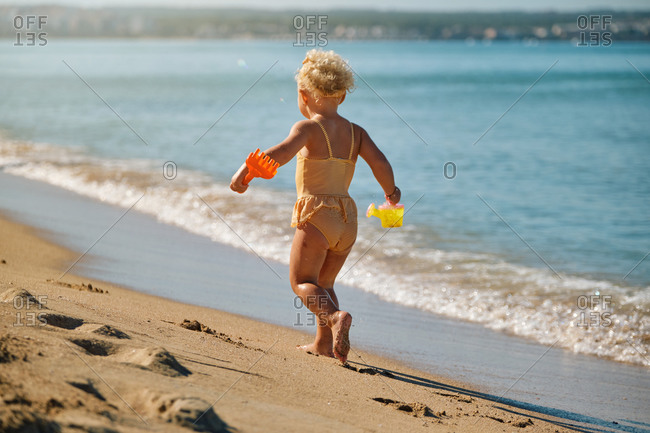 Little girl in a yellow and white striped swimsuit running towards the sand of the sea with plastic toys in her hands