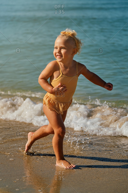 Vertical photo of a girl in a yellow and white striped swimsuit with a hair band running down to the seashore with an expression of happiness on a sunny day