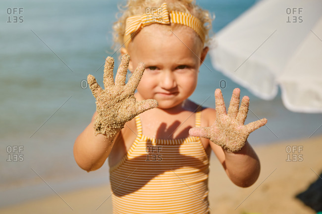 Selective focus on a little girl's sandy hands at the beach on a sunny day