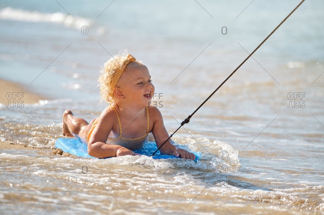 Little girl with a swimsuit and headband lying on a surfboard at the edge of the beach playing while someone drags her along the waves