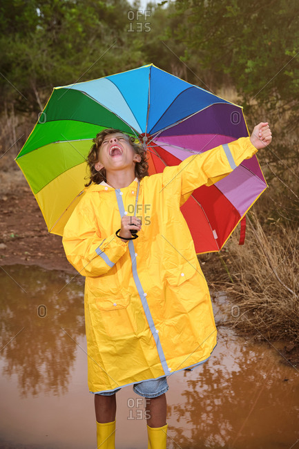 Vertical photo of a blond boy in a raincoat with yellow water boots and a colorful umbrella in the rain in a puddle in the forest screaming happy with his arm raised