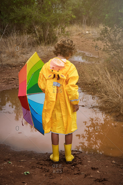 Vertical photo of a blond boy on his back in a yellow raincoat with a hood with a donkey and yellow water boots and a colorful umbrella in the rain in a puddle in the forest