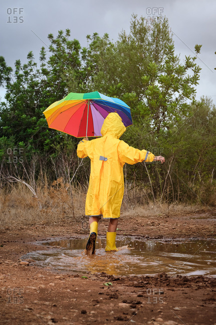 Vertical photo of a child on his back with a yellow raincoat and a colorful umbrella playing in a puddle with rain boots in the middle of the forest