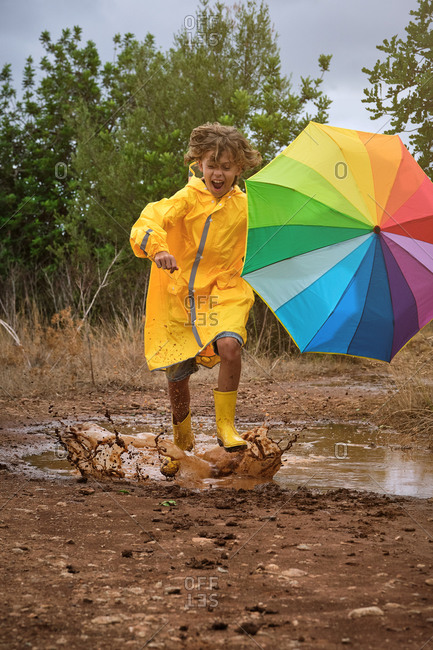 Vertical photo of a child with a yellow raincoat and a colorful umbrella playing in a puddle splashing the water with the rain boots in the middle of the forest