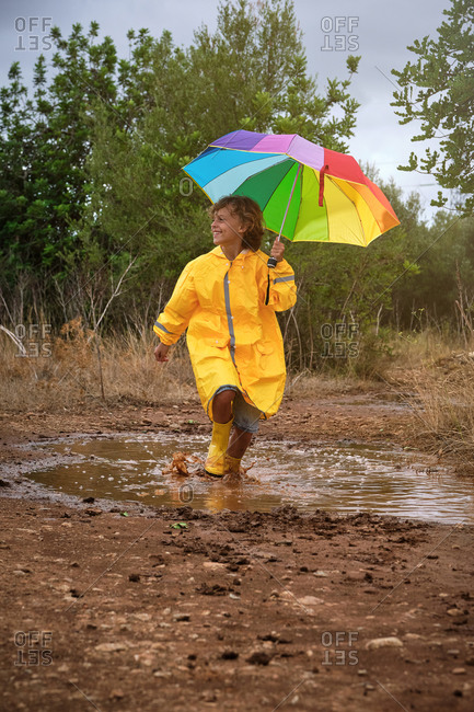 Vertical photo of a child with a yellow raincoat and a colorful umbrella playing in the middle of a puddle with the rain boots in the forest