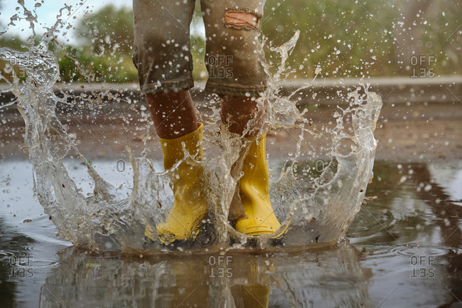 Detail of yellow rain boots hitting a puddle splashing water in a forest