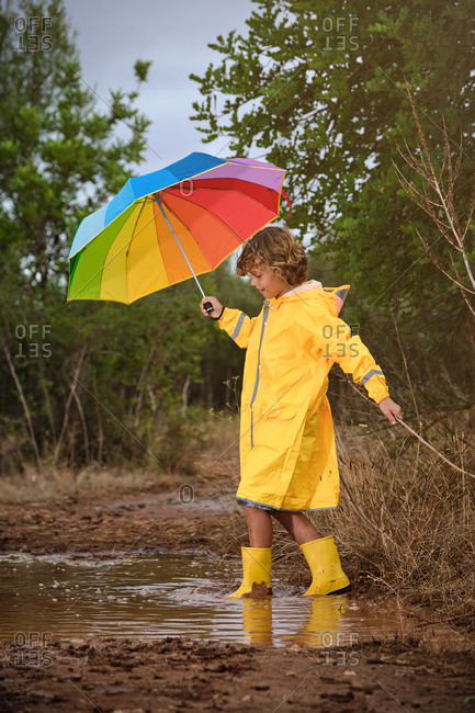 Vertical photo of a blond boy with a yellow raincoat, rain boots and a colorful umbrella playing with a stick and a puddle in the forest