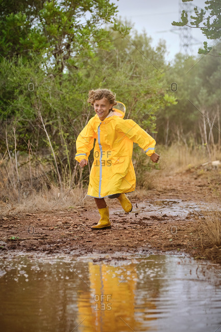 Vertical photo of a blond boy in a raincoat and yellow rain boots running along a path full of puddles in the forest while smiling