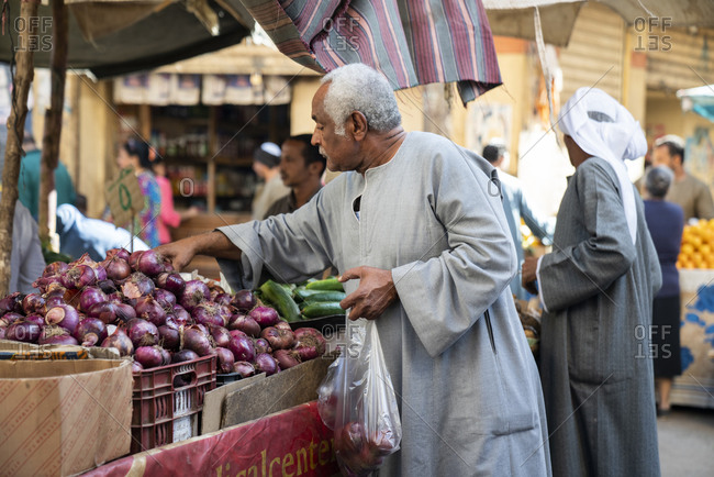 Luxor, Luxor Governorate, Egypt - December 24, 2017: Egyptian male buying onions at a market