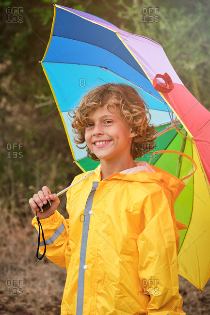 Vertical photo of a blond boy with curly hair in a yellow raincoat holding a colored umbrella while smiling on camera in the middle of a forest