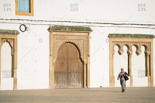 Essaouira, Marrakesh-Safi, Morocco - December 27, 2017: Woman walking by Moroccan fortress wall