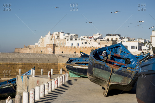 Essaouira, Marrakesh-Safi, Morocco - December 27, 2017: Colorful fishing boats in front of Moroccan town
