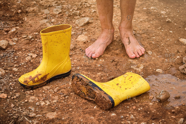 Dirty muddy bare feet with a pair of water boots next to them on a muddy road on a rainy day