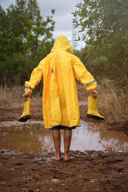 Vertical photo of a child in her back with yellow raincoat walking on a barefoot muddy path with water boots in his hands in a forest