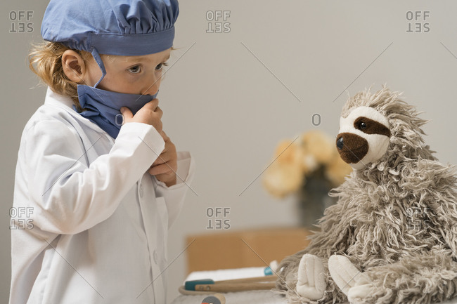 Young child in medical PPE adjusts face mask and examines a plush toy sloth