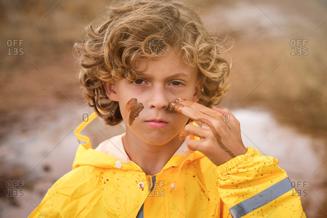 Blond boy with curly hair in a yellow raincoat drawing marks on his face with the mud looking at the camera seriously in the middle of the forest