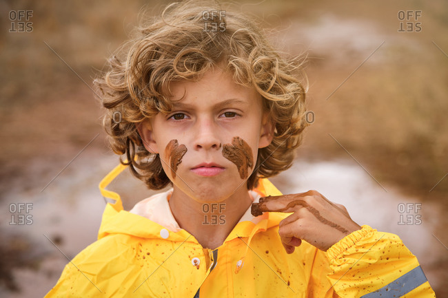 Blond kid with curly hair in a yellow raincoat drawing marks on his face with the mud looking at the camera with serious expression in the middle of the forest