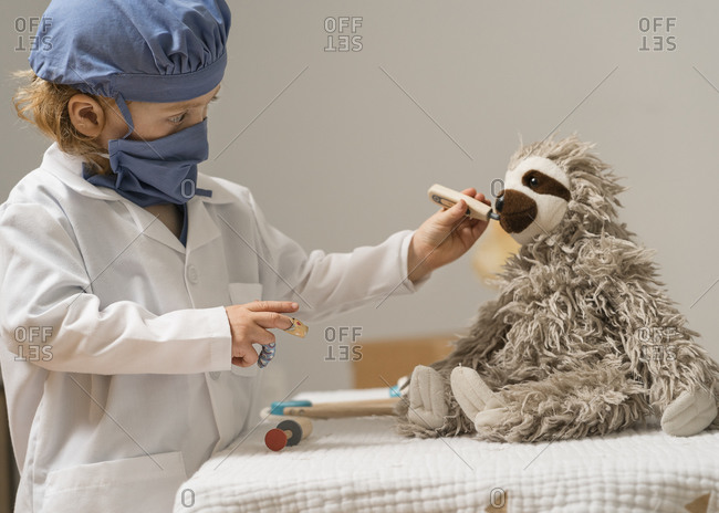 Young child in medical PPE examines a plush toy rabbit by taking its temperature with a thermometer
