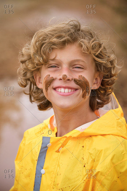 Blond kid with curly hair in a yellow raincoat with marks on his face with the mud looking at the camera with serious expression in the middle of the forest