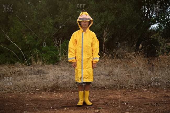 Portrait of a blond boy in a yellow hooded raincoat and yellow rain boots standing in the middle of a forest on a rainy day